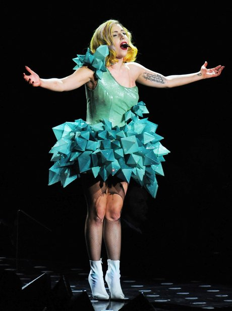 Lady Gaga performs in a green dress live on stage