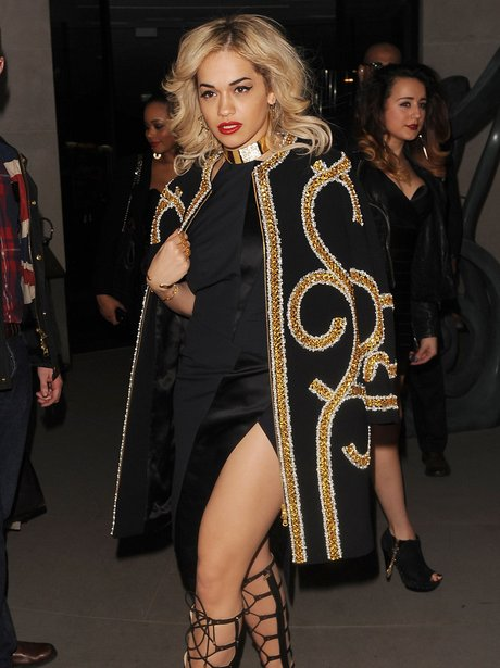 Rita Ora wearing a gold and black jacket at London Fashion Week 2013