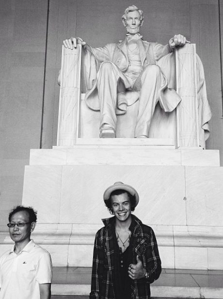 Harry Styles poses next to the Lincoln Memorial