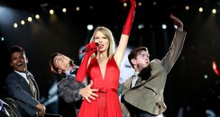Taylor Swift on stage in a red dress
